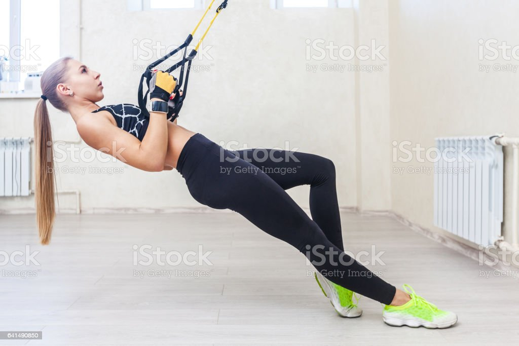 Mädchen in einem Jim tun Übungen mit trx – Foto