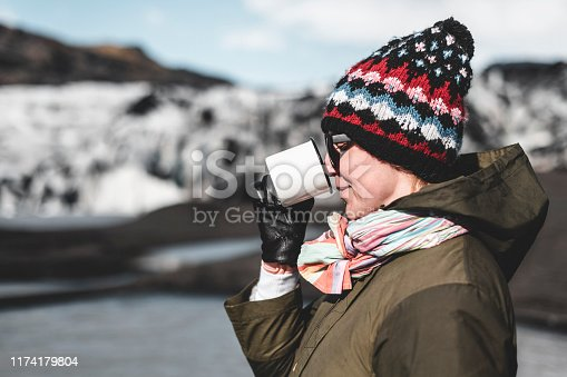 A girl in a khaki jacket is drinking from a white metal mug. In the background a glacier.