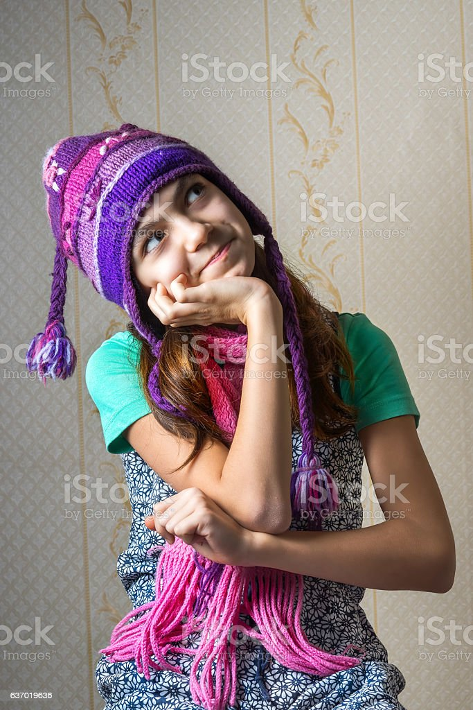 girl in a knitted hat and scarf, looking up pensively. stock photo