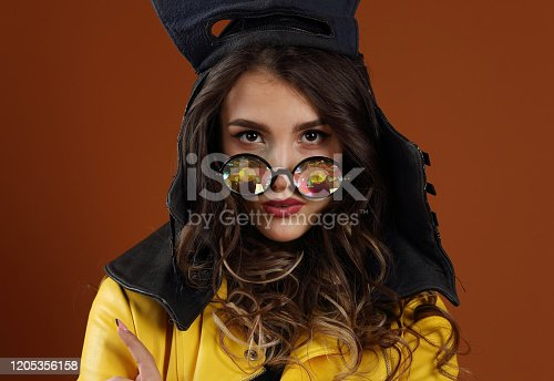 Studio portrait of a beautiful girl in a leather motorcycle helmet and kaleidoscope glasses