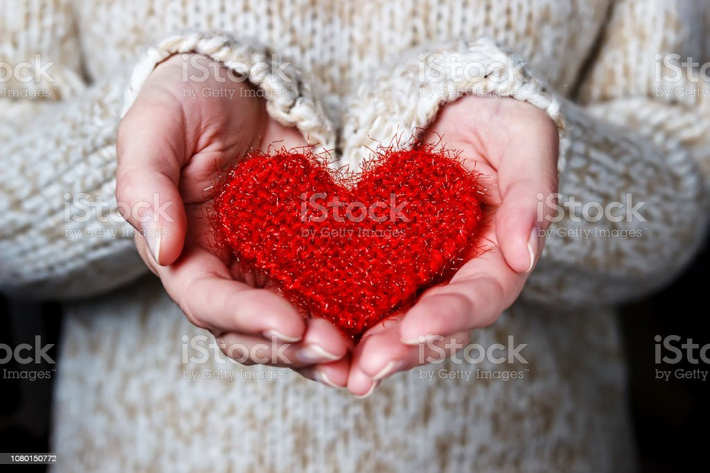 Girl in a light sweater gives a knitted heart. Girl in a light sweater gives a knitted heart. Close-up A Helping Hand Stock Photo