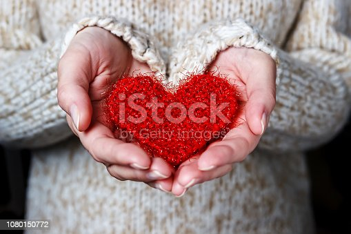 Girl in a light sweater gives a knitted heart. Close-up