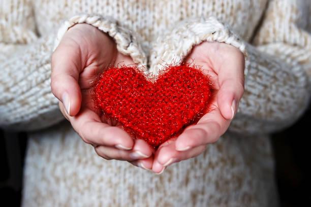 flicka i ljus tröja ger ett stickade hjärta. - omsorg bildbanksfoton och bilder