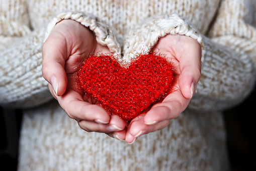 Girl In A Light Sweater Gives A Knitted Heart Stock Photo - Download Image Now