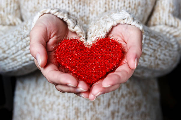 Girl in a light sweater gives a knitted heart. Girl in a light sweater gives a knitted heart. Close-up amor stock pictures, royalty-free photos & images