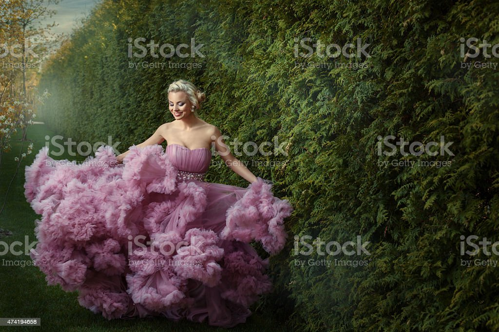 Girl in a magnificent dress dances. stock photo