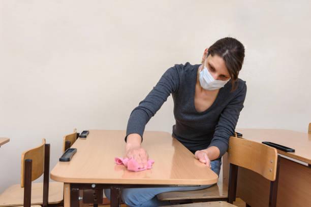 het meisje in een medisch masker wast lijsten in een schoolklasse tijdens de quarantaineperiode - tears corona stockfoto's en -beelden