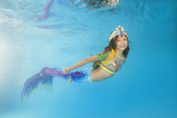 A girl in a mermaid costume poses underwater in a pool. Young beautiful girl poses underwater in the pool. stock photo