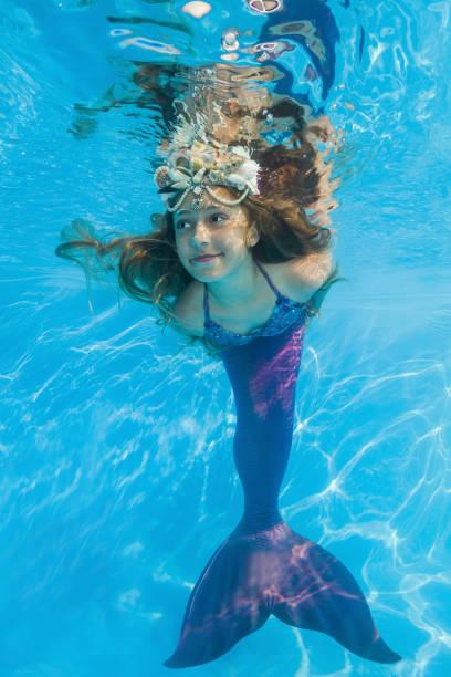 girl in a mermaid costume poses underwater in a pool. Young beautiful girl poses underwater in the pool. stock photo