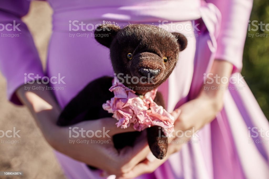 Girl in a pink dress holding a Teddy bear in her hands. Girl says...