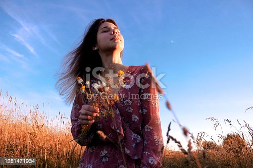 A beautiful, confident girl holding a bouquet of wildflowers in her hands. Her hair is blowing away the wind. She is wearing a pink dress. Nature is around her. A field with high yellow grass. You can read confidence and calmness on the girl's face. Photo taken at sunset with bottom view