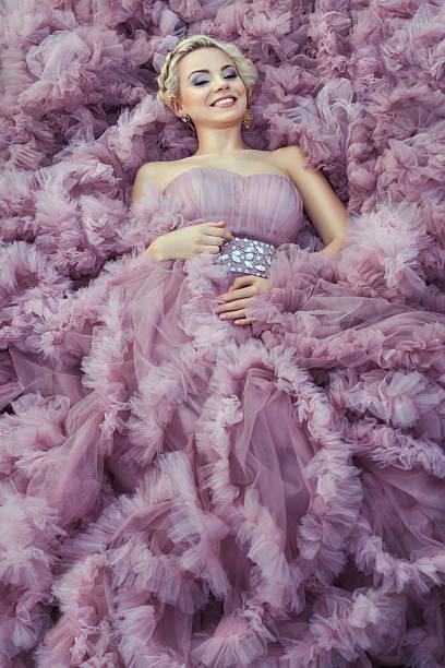 mädchen in einem rosa kleid lächelnd. - tüllkleid stock-fotos und bilder