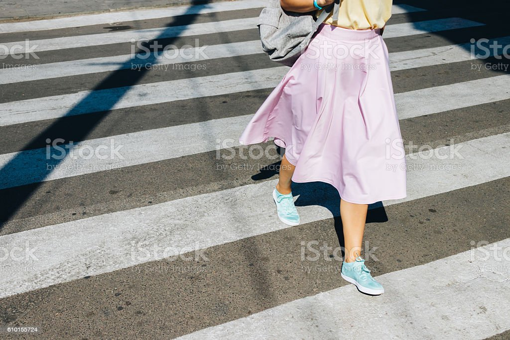 Girl in a pink skirt and sneakers crossing the road stock photo