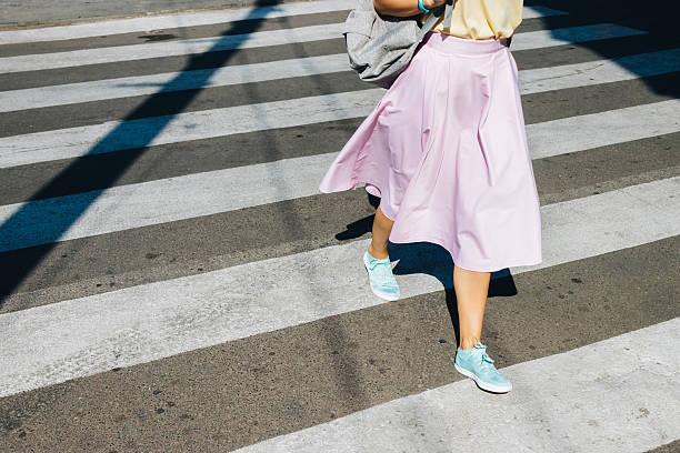 girl in a pink skirt and sneakers crossing the road - spódnica zdjęcia i obrazy z banku zdjęć