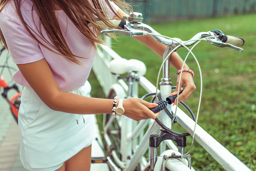 Girl in a pink T-shirt near the fence in the summer in the park. Locks, locks the cable with a code number. Protection against hijackings and scammers and thieves. Safety bike in the city.