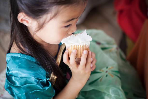 eine mädchen in einer prinzessin kostüm wird einen cupcake essen. - prinzessinnen torte stock-fotos und bilder