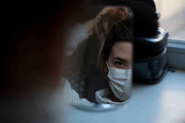 meisje in een beschermend masker in de weerspiegeling van de spiegel.   coronavirisus bescherming. covid-19. covid-20. - mirror mask stockfoto's en -beelden