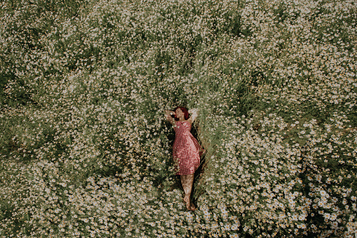 A girl in a red dress lies in a field of daisies. The concept of outdoor recreation, summer harmony, natural beauty, retro style.
