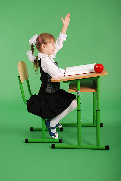 girl in a school uniform sitting at a desk - one girl only stock photos and pictures