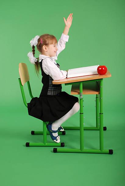 Fille en uniforme de l'école assis à un bureau - Photo