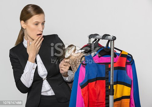 672064598istockphoto Girl in a strict office suit, examines clothes 1079747488