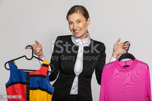 672064598istockphoto Girl in a strict office suit, holding clothes 1079746710
