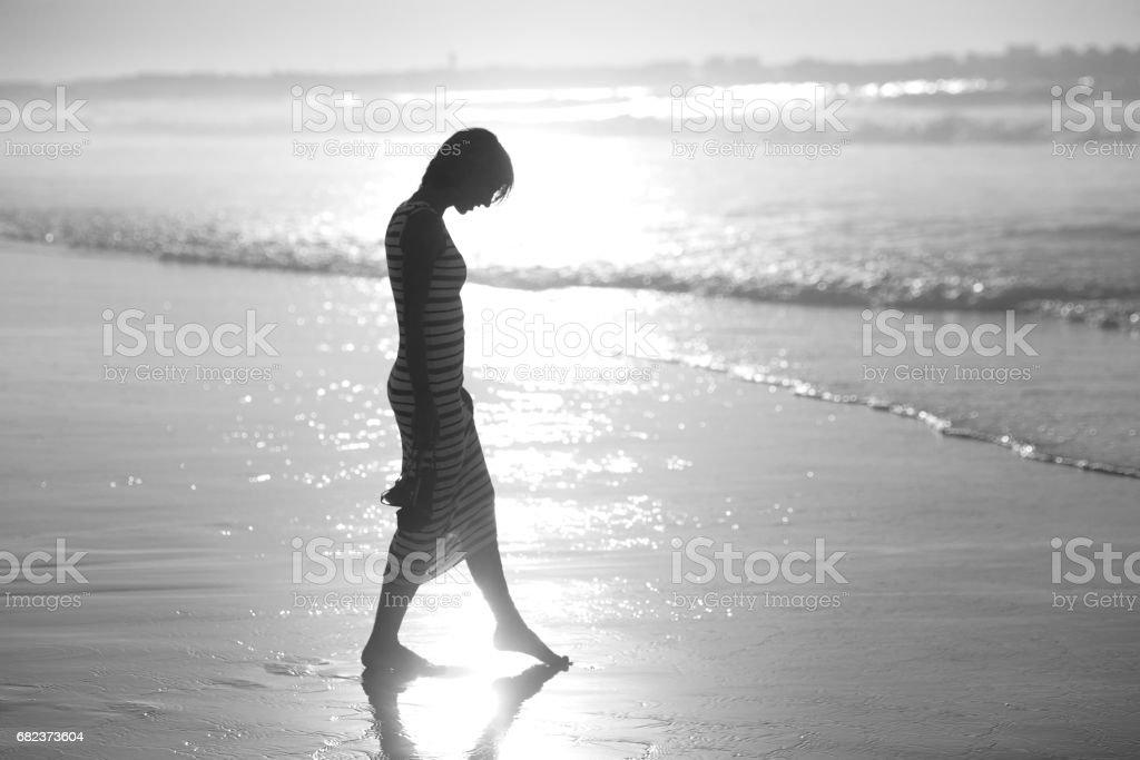 A girl in a summer dress is walking along the ocean foto stock royalty-free