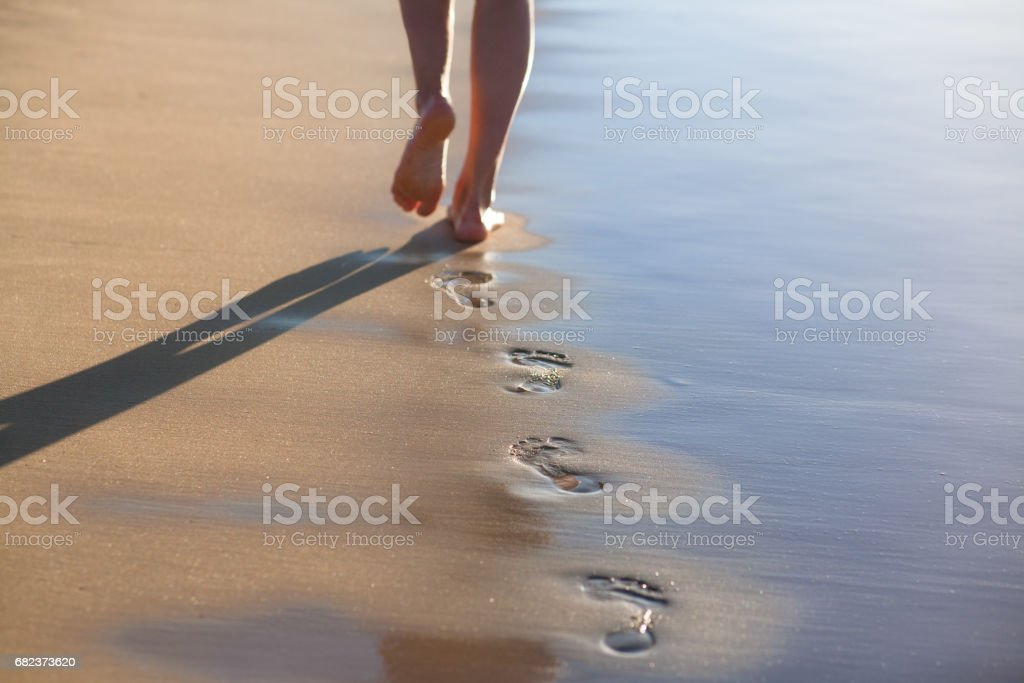 A girl in a summer dress is walking along the ocean royaltyfri bildbanksbilder