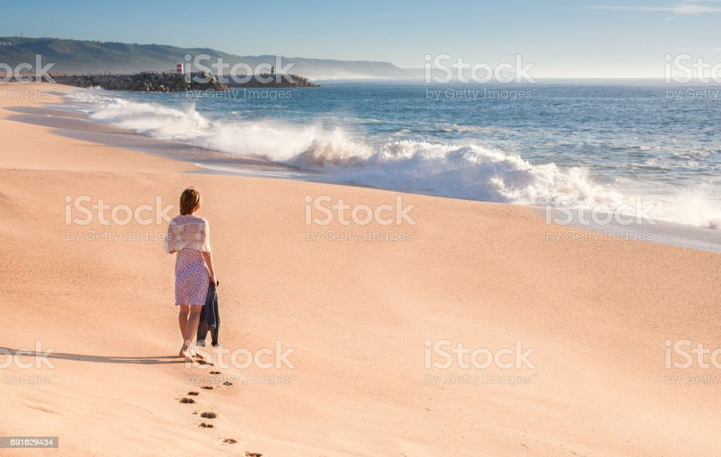 A girl in a summer dress is walking along the ocean stock photo