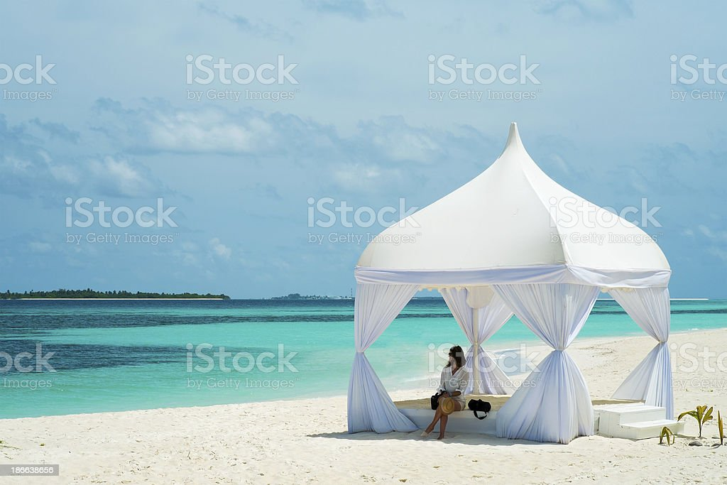 Girl in a tent on the shores of azure ocean stock photo