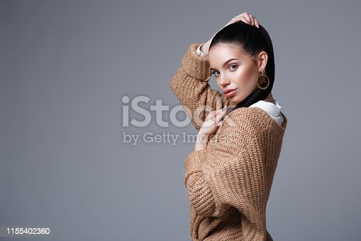 Beautiful girl with a sports figure. full-length Studio portrait of a stylish young girl in a sweater on a gray background. Studio photo horizontal.