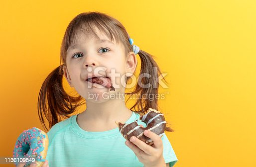 Girl in a turquoise shirt eat donuts.Yellow background. Copy space.