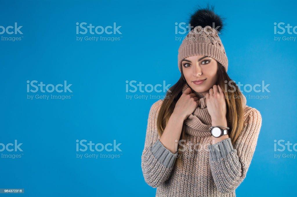 Meisje in een warme trui, sjaal en muts op een blauwe achtergrond - Royalty-free Alleen volwassenen Stockfoto