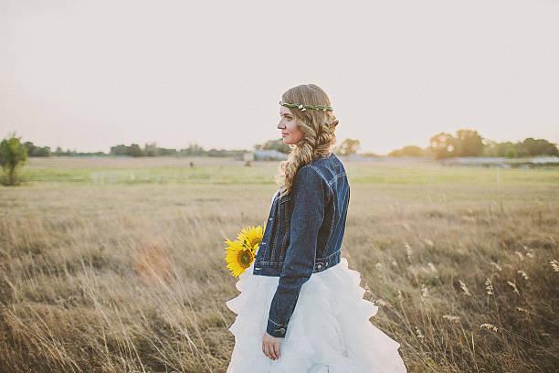 mädchen in ein hochzeitskleid und jeans-jacke mit sonnenblumen - bräutigam jeans stock-fotos und bilder