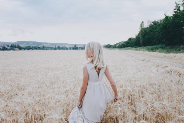 Girl in a wheat field. Back view. stock photo