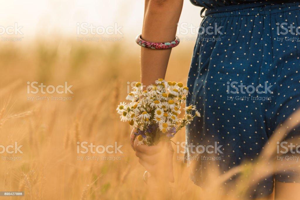 Garota em um campo de trigo com buquê de flores. - foto de acervo
