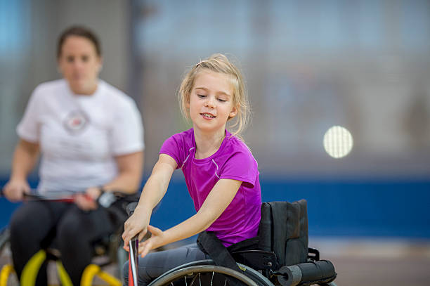 girl in a wheelchair playing sports - wheelchair sports stock photos and pictures