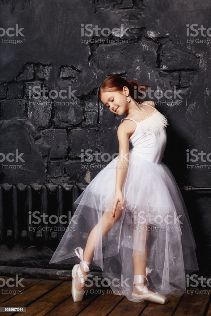 Girl in a white ball gown and shoes, beautiful red hair. Young theater actress. Little prima ballet. Young ballerina girl is preparing for a ballet performance stock photo