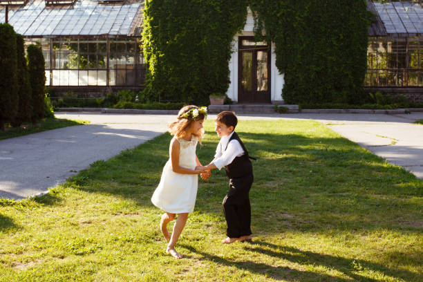 eine mädchen in einem weißen kleid tanzt mit einem jungen in einem modischen anzug. - hochzeitsfeier mit kindern stock-fotos und bilder