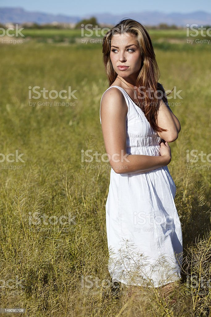 Girl in a white dress posing by wheat field. stock photo