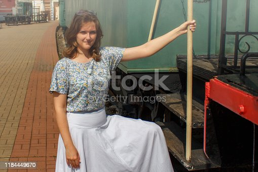 Girl in a white dress sits on the train. Woman is preparing to sit in the car. Farewell before sending the train on platform. Vintage style and retro train of late 19th, early 20th centuries.