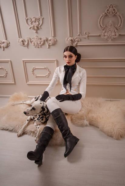 ein mädchen in einem weißen strengen anzug, sitzt auf dem boden und streichelt liebevoll seinen dalmatinischen hund. hintergrund klassischer lichtinnenraum - königin kopfteil stock-fotos und bilder