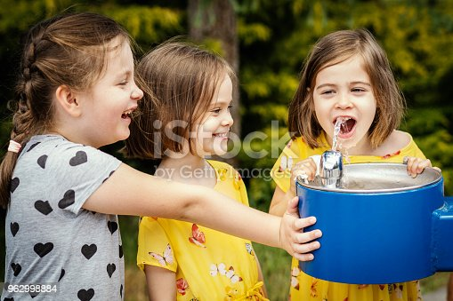 little beautiful girl in a yellow dress drinks water from a fountain in the park