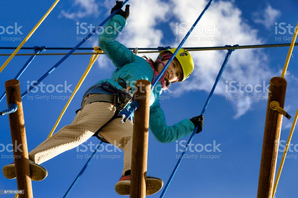 A girl in a yellow helmet plays in an adventure park. stock photo