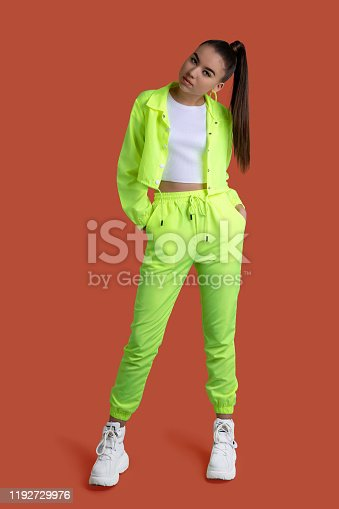 Girl in a yellow neon tracksuit on a colored background