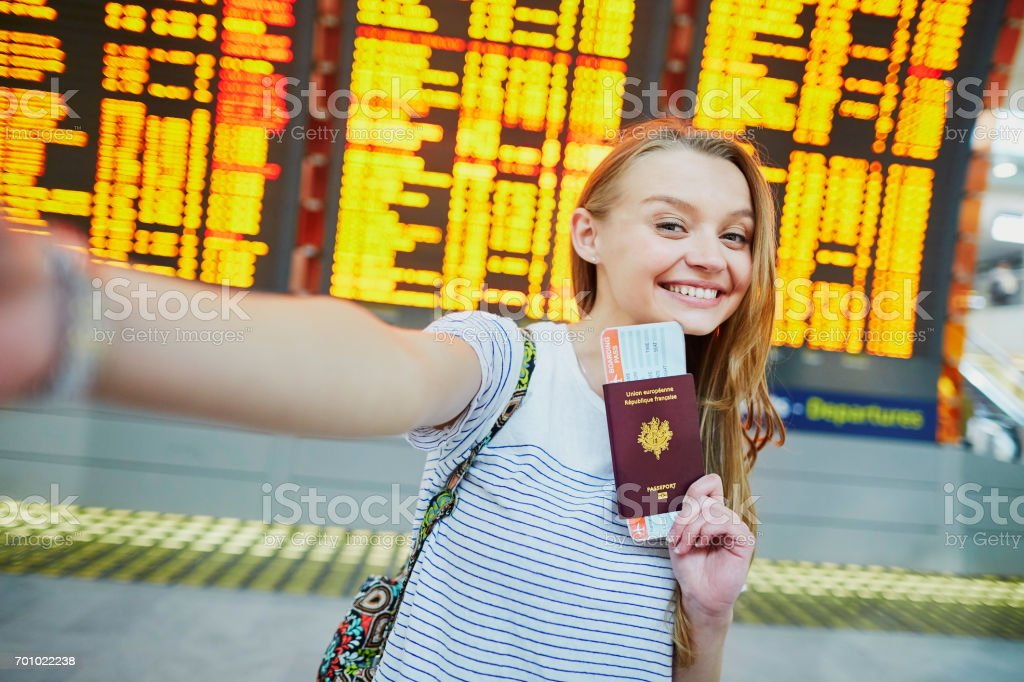Girl in airport, taking selfie with passport and boarding pass stock photo