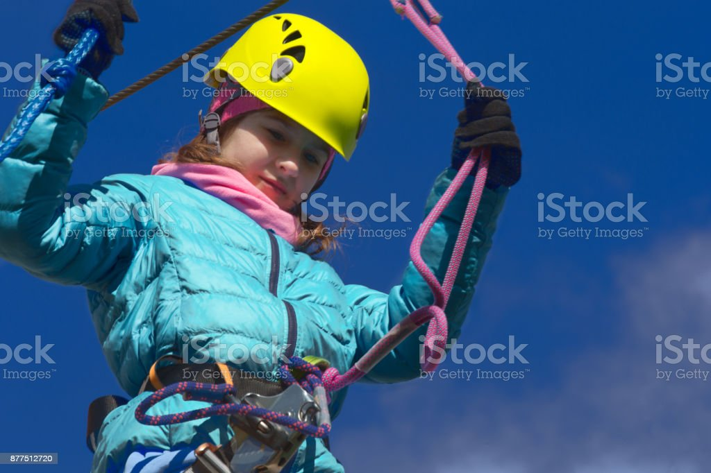 A girl in an adventure park climbs staircase. stock photo