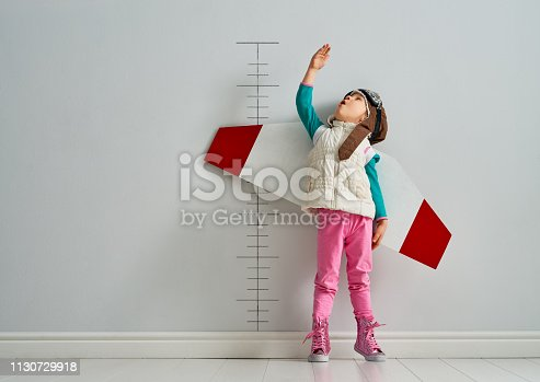 Little child is playing pilot. Kid is measuring the growth on the background of wall.
