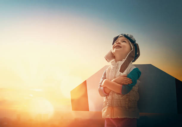 girl in an astronaut costume Little child playing pilot. Girl on the background of sunset sky. Kid in an astronaut costume dreaming of becoming a spaceman. dreamlike stock pictures, royalty-free photos & images