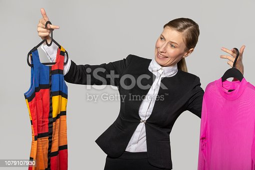 672064598istockphoto A girl in an office suit examines colored dresses 1079107930